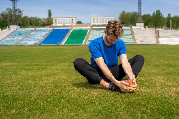 Спортсмен делает упражнения на растяжку на стадионе перед летними тренировками