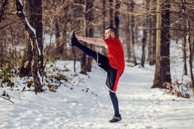 Sportsman doing stretching and warm up exercises while standing in woods at snowy winter day
