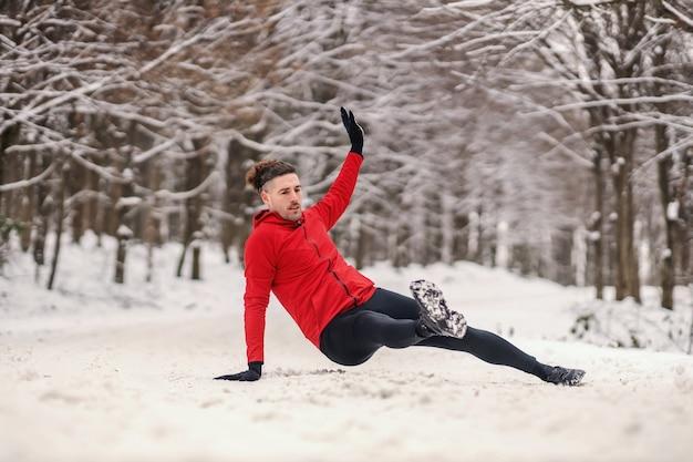 森の中で雪の降る冬の日にウォームアップ運動をしているスポーツマン。冬のフィットネス、健康的な生活