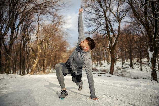 雪の降る冬の日に自然の中でウォームアップ運動をしているスポーツマン。ウィンタースポーツ、雪の降る天気、ウォームアップの練習