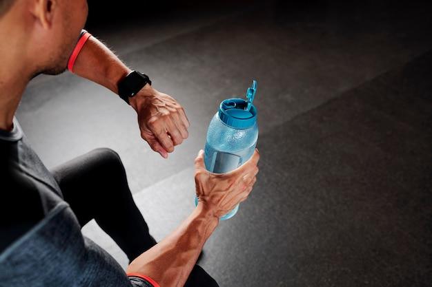 Спортсмен пьет воду и проверяет умные часы