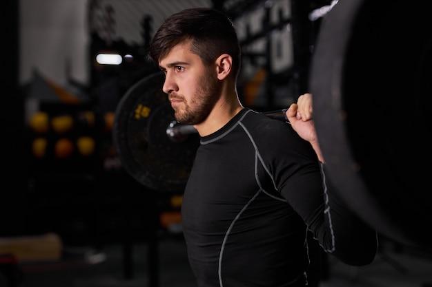 バーベルで運動するスポーツマン。暗いジムでウェイトリフティングトレーニングをしている若い白人の筋肉質の男性ボディービルダー、スポーツ用品を使用して、側面を見ている男性スタンド、側面図