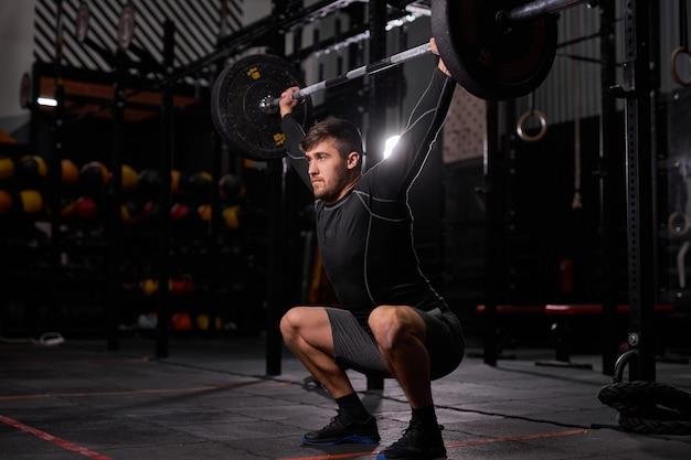 バーベルで運動するスポーツマン。スポーツ機器を使用して、暗いジムでウェイトリフティングトレーニングを行う若い白人の筋肉質の男性ボディービルダー