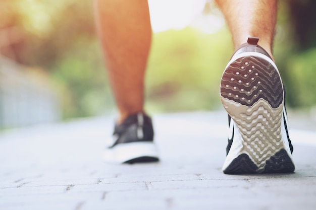 屋外で走るスポーツマンのフットランナートレイル。自然と石の秋のトレイルで上り坂のフィットネスジョギングトレーニングを実行している男の後ろの靴にクローズアップ。健康的なライフスタイルとスポーツの概念を行使する