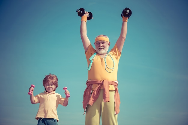 スポーツマンの祖父とダンベルを持った健康な子供は、ヘルスケアの陽気なライフスタイルスポーツと...