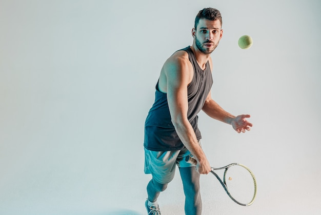 Sportsman hitting tennis ball with racquet. young bearded european tennis player is focused on game. isolated on turquoise background. studio shoot. copy space