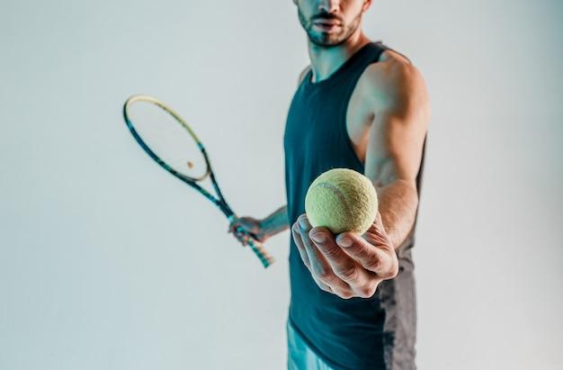 Спортсмен удерживает и показывает теннисный мяч в руке крупным планом. обрезанный вид молодого бородатого теннисиста. изолированные на сером фоне с бирюзовым светом. студийная съемка. копировать пространство