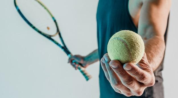 Спортсмен держит и показывает в руке теннисный мяч