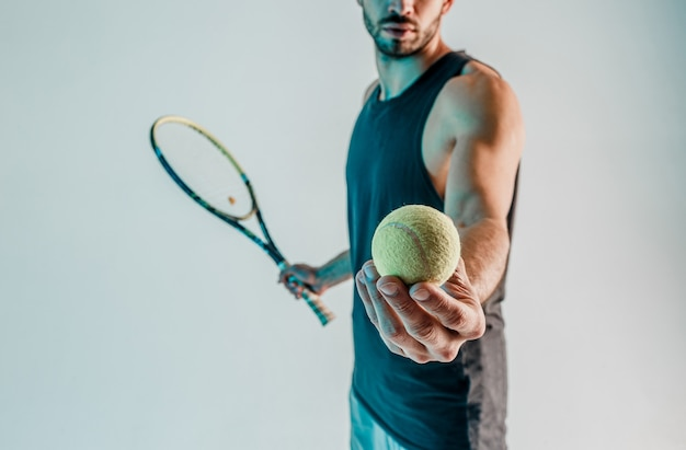 Sportsman hold and showing tennis ball in hand close up. cropped view of young bearded tennis player. isolated on gray background with turquoise light. studio shoot. copy space