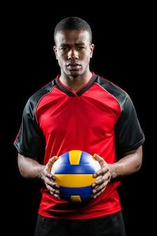 Спортсмен держит мяч для волейбола