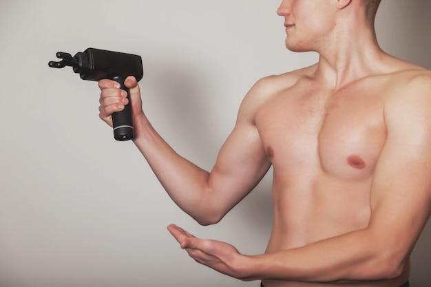 스포츠맨은 체육관의 의료 사무실에서 스포츠 총 충격 마사지를 보유하고 있습니다. 선수 홈 마사지 운동. 신체의 재생 마사지를 위한 타악기 요법. 부상 재활의 개념입니다. 복사 공간