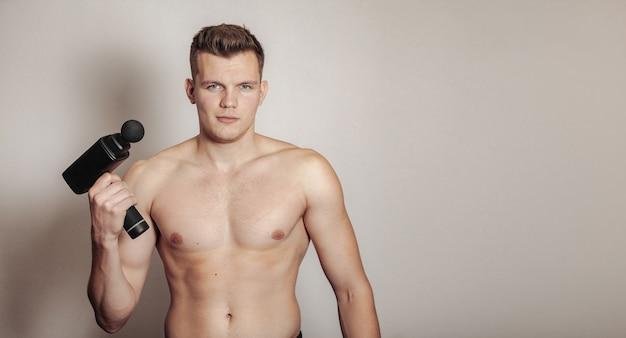 Sportsman holds sports gun shock massage in medical office of gym. athlete home massage exercises