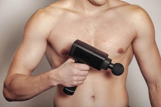 Sportsman holds sports gun shock massage in medical office of gym. athlete home massage exercises.