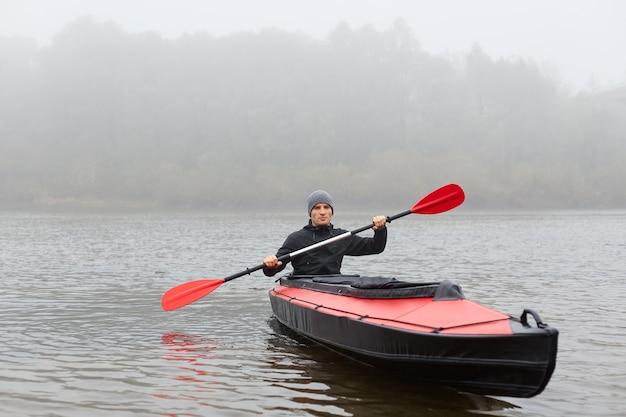 Спортсмен в серой кепке и черной куртке держит в руках весло, смотрит вдаль, активно проводит свободное время.