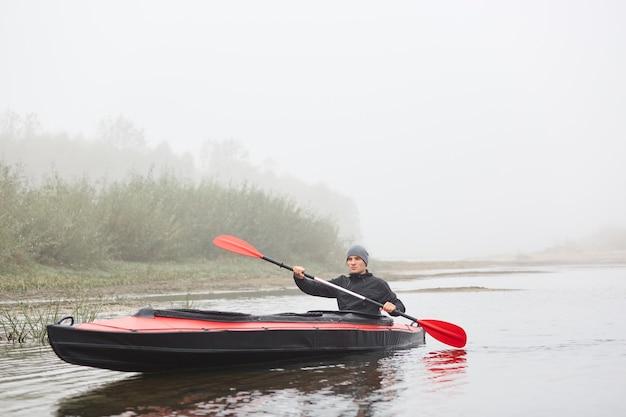カヤックのスポーツマン、霧の川でパディング、屋外で自由な時間を過ごし、ウォータースポーツをし、オールを手にポーズをとる