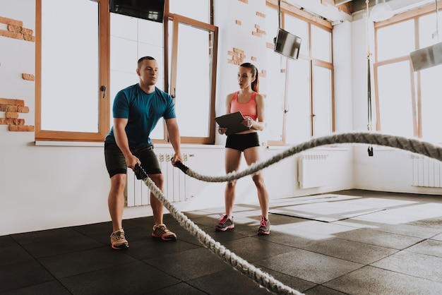 Sportsman is exercising in gym with trainer
