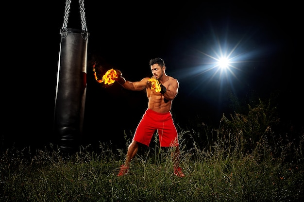 Sportsman is training on the black night background muscular body boxing gloves in the fire the night training training in open space on grass boxing kick from the right hand black punching bag