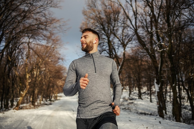 Sportsman jogging in forest on snowy trail at winter. healthy lifestyle, winter fitness