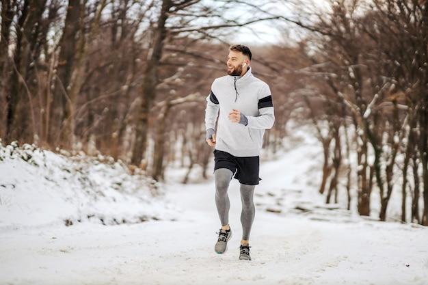 겨울에 숲에서 눈 덮인 길에 조깅 하는 스포츠맨. 겨울 스포츠, 건강한 습관, 야외 활동