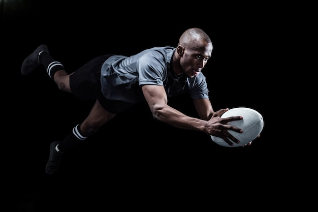 Sportsman jumping for catching rugby ball