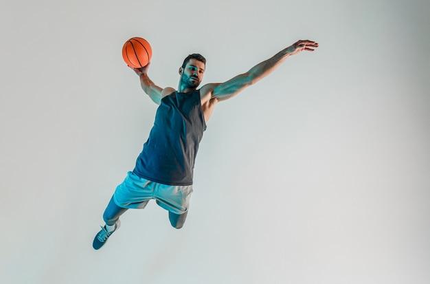 スポーツマンがジャンプしてバスケットボールのボールを投げたいと思っています。真面目な若いひげを生やしたヨーロッパのバスケットボール選手。ターコイズブルーの光で灰色の背景に分離。スタジオ撮影。コピースペース