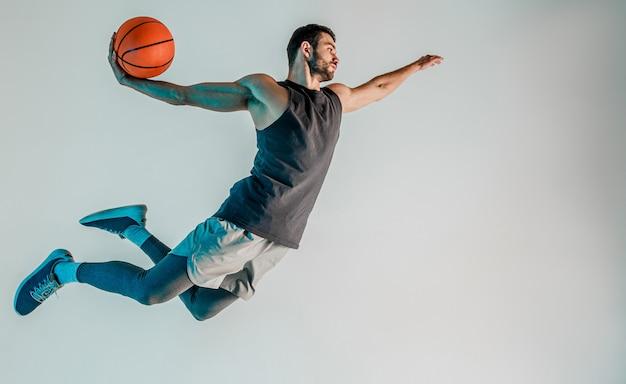 Спортсмен прыгает и хочет бросить баскетбольный мяч. вид сбоку сконцентрированного молодого бородатого европейского баскетболиста. изолированные на сером фоне с бирюзовым светом. студийная съемка. копировать пространство