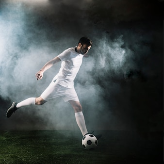 Sportsman kicking soccer ball in smoke