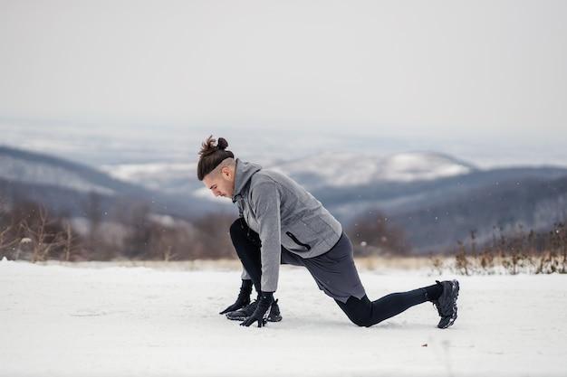 스포츠맨은 무릎을 꿇고 눈 덮인 겨울 날 자연에서 달리기 시작할 준비를 합니다. 겨울 피트니스, 유산소 운동