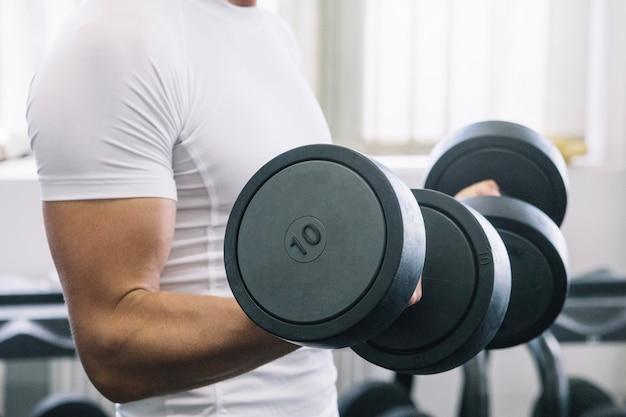 Sportsman lifting dumbbells