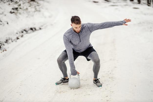 冬の雪道で自然の中でしゃがみながらケトルベルを持ち上げるスポーツマン。
