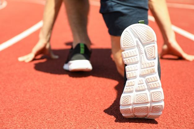 Спортсмен низко начинает бегать по красной спортивной трассе, крупный план