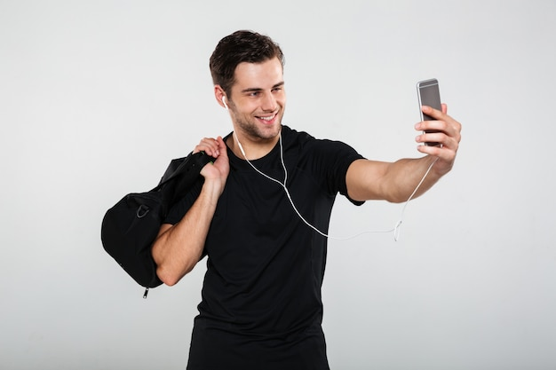 Sportsman make selfie with bag by mobile phone listening music