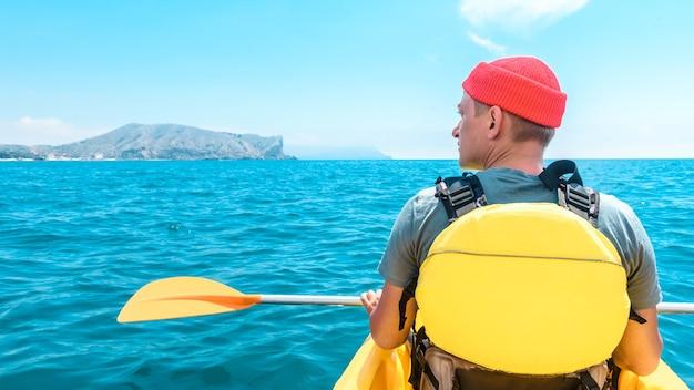 スポーツマンの男は海のボートで漕ぐスポーツに行きます。スポーツと旅行のコンセプト