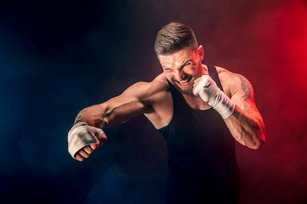 Sportsman muay thai boxer fighting on black background with smoke.