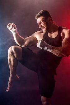 Sportsman muay thai boxer fighting on black wall with smoke.