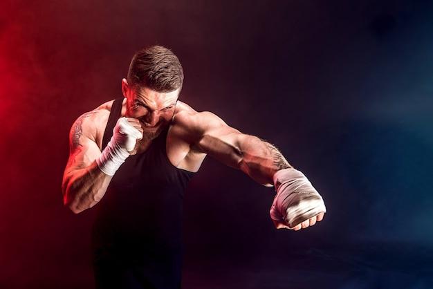 煙で黒い壁で戦うスポーツマンムエタイボクサー。スポーツコンセプト。