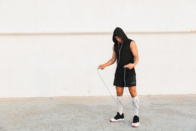 ビーチで屋外のスポーツマンは、機器を使ってスポーツエクササイズをします。
