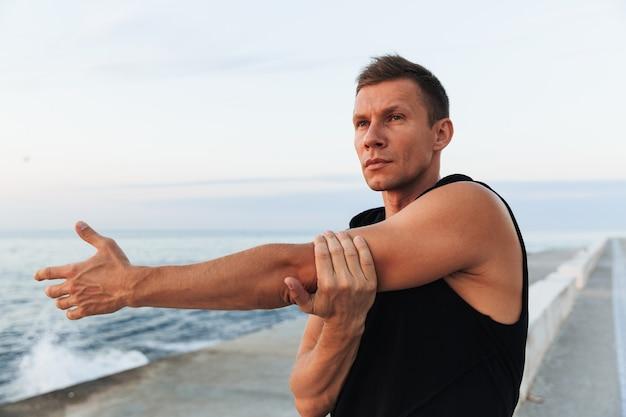 ビーチで屋外のスポーツマンはストレッチ体操をします。