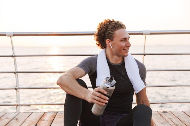 水を飲むイヤホンで音楽を聴いて座っているビーチで屋外のスポーツマン。