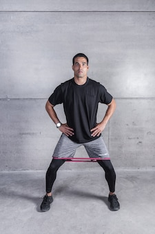Sportsman performing exercise with elastic band on legs
