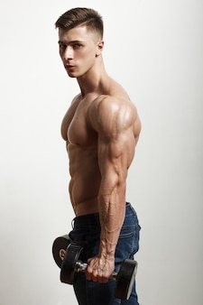 Sportsman performing exercises with dumbbells Premium Photo