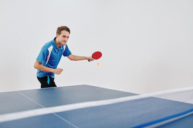 Спортсмен, играя в настольный теннис