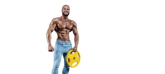 Спортсмен позирует изолированным на белом в джинсах с гантелью в руке