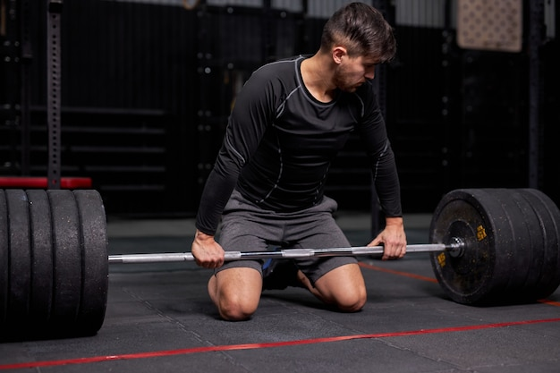 フィットネスジムでバーベルの重量を持ち上げる準備をしているスポーツマン。スローガンやテキストメッセージを宣伝するためのコピースペース領域。ファンクショナルトレーニングとクロスフィットのコンセプト。