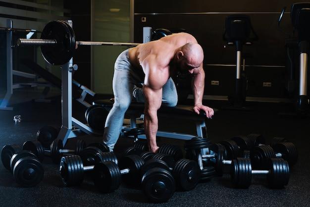 Спортсмен готовится поднять гантель