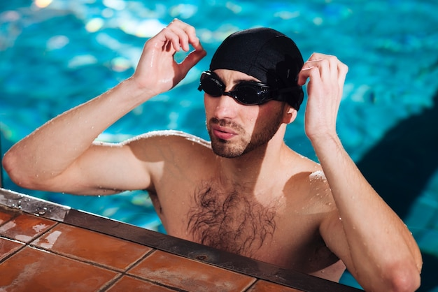 Sportsman putting on swimming goggles
