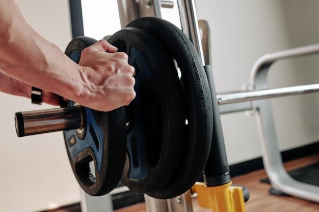 Спортсмен кладет весовые пластины на штангу