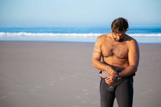 Sportsman putting on wetsuit for surfing on ocean beach and taking off watch