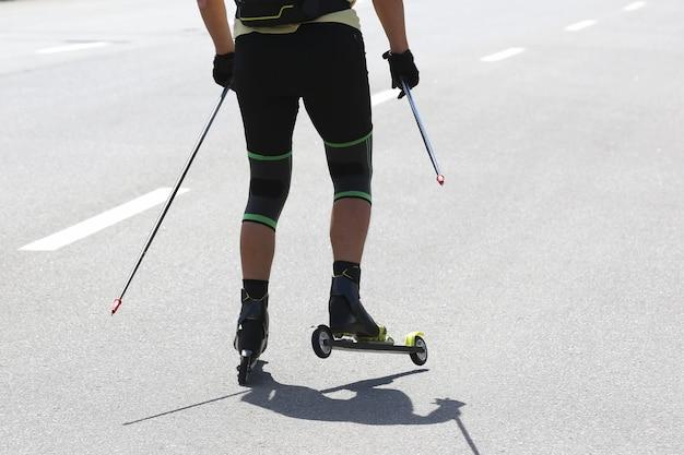 街道のアスファルトでスポーツマンのローラースキー。スポーツレジャー