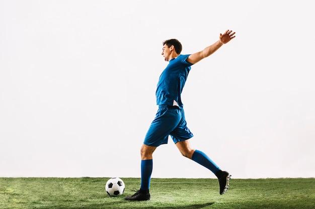 Sportivo che corre e calcia la palla